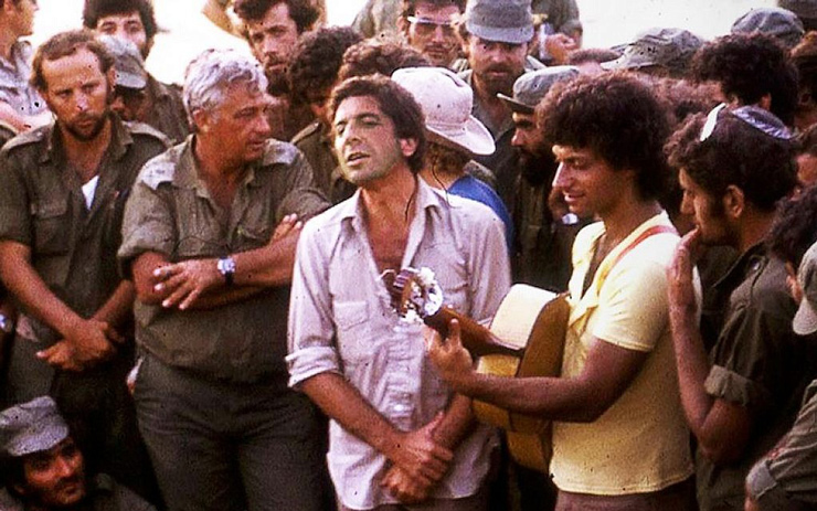 Leonard Cohen, center, performing with Israeli singer Matti Caspi, on guitar, for Ariel Sharon, with arms crossed, and other Israeli troops in the Sinai in 1973. (Courtesy of Maariv via JTA)