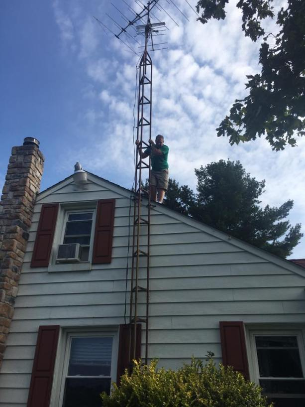 An old tv radial antenna that a friend standing on the roof is about to push over