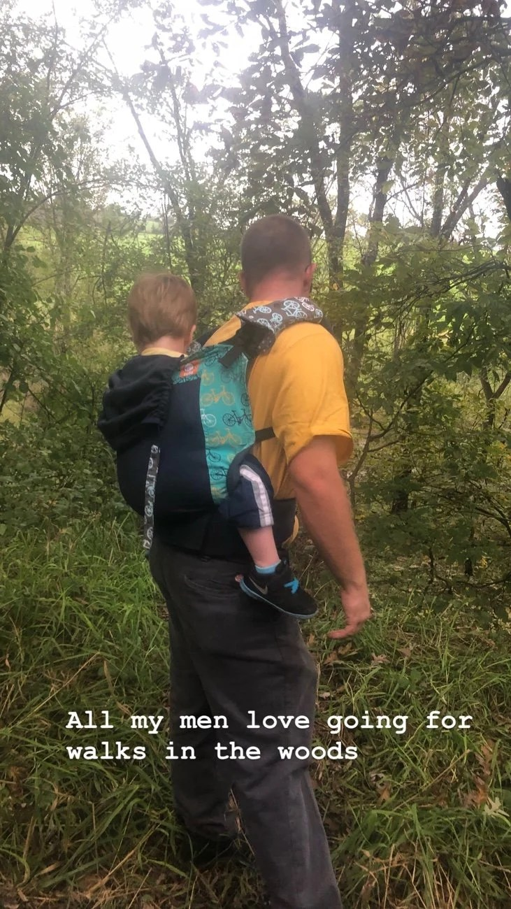 Asher on Daddy's back while walking on a grass abandoned road.  Asher is in a Tula baby carrier overlooking a stream .