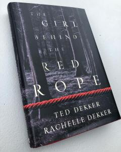 The Girl Behind the Red Rope book cover laying on table
