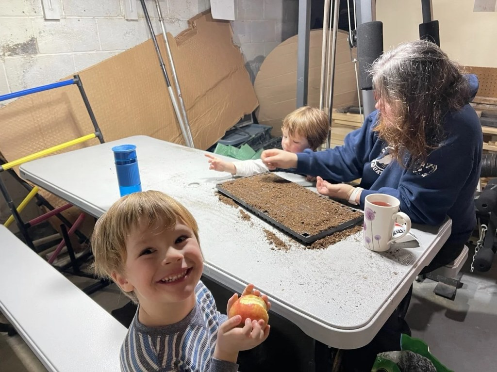 4 year old blond boy smiling snacking on an apple while mom helps 3 year old plant seeds