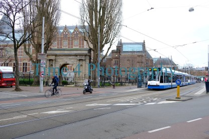Modern, blue and white tram entering in theright side of the picture on a big avenue in Amsterdam, Holland, with some buildings on the left side