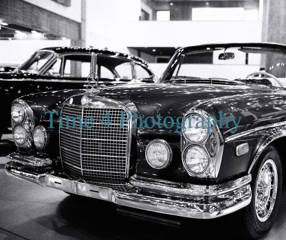 1963 Mercedes Benz 300 SE black convertible at a car show , with front and side view, and this is a black and white picture