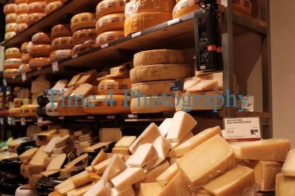 Big assortment of yellw cheese in Amsterdam , in round forms and in cut pieces, displayed on shelves inside a cheese-shop.