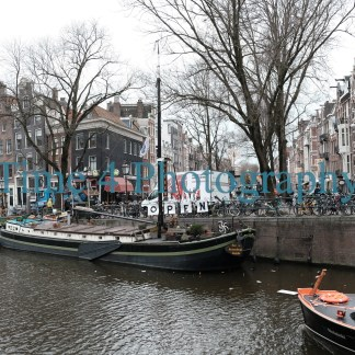 Boats anchored in a Canal in Amsterdam, Holland, in wintertime. In the background there are many parked bicycles and typical buildings.