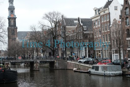 Canal in Amsterdam during daytime, showing boats anchored , houses , a bridge and the tower of a church along its borders.