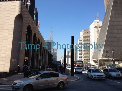 A business day at the famous Paulista Av. in Sao Paulo, Brazil. There are some cars on the street and a deep blue sky. The sun lights some tall buildings.