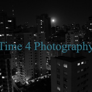 Black and white picture showing tall buildings with lighted windows in a dark night and at a full moon in Sao Paulo, Brasil.