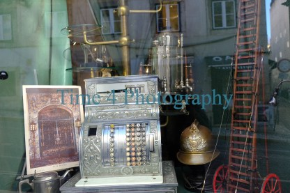 Antique cash register and other vintage objects in a show window in Portugal