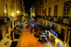 Downtown street at night in Lisbon,Portugal, showing cafes, discotheque, people on the street and cars parked along the curb