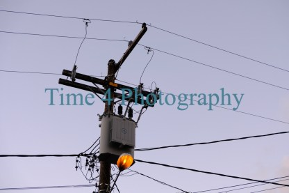 An utility pole with several cables and a lighted streetlamp. The picture was taken in Salvador da Bahia, in Brazil,where electric cables are mostly aereal.