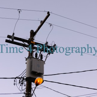 Utility pole with several cables and a lighted streetlamp