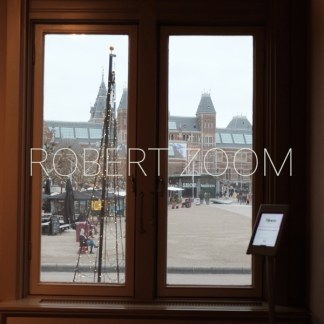 The famous Rijksmuseum of Amsterdam, seen through a window in winter. It is drizling outside and the day is rather dark.