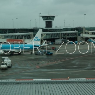 A KLM plane can be seen parked on the left side of the apron. On the background is the control tower and the airport building