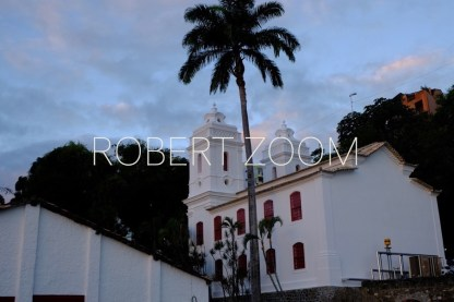 A small romantic white church with red windows located under a tall palmtree in the tropical city of Salvador da Bahia, in Brazil.