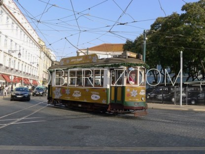 In Chritmas time, a streetcar is passing in front of some low old buildings in downtown Lisbon. A Santa Claus is piloting the streetcar.