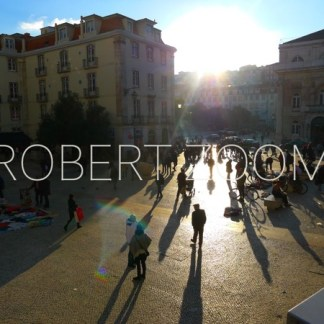 At sunset, many people are walking in a big square in Lisbon, Portugal. Sunglare and long shadows give an impressive effect to the picture.