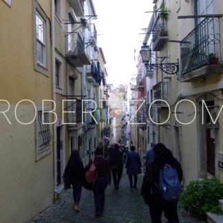 Old narrow street in Lisbon,Portugal, on which there is a group of people walking