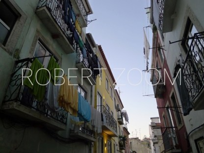 In a narrow alley in Lisbon, clothes in various colors hang from windows of old buildings. It is almost night in Portugal.
