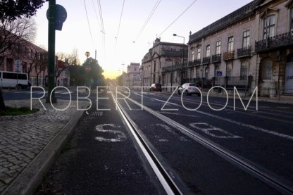 Tram rails stretched along a street in Lisbon, Portugal. On the right a row of grey houses,in the background the last glow of a setting sun.
