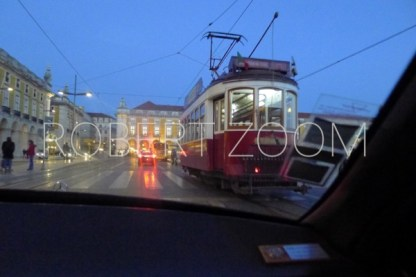 A streetcar is riding on an avenue in Lisbon downtown.It is already dark at night and the streets reflect the tail lights from passing cars.