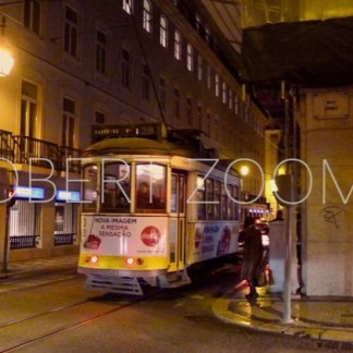 A yellow streetcar is approaching a street corner of Lisbon, at night. The streetlamps are on and the streets deserted.