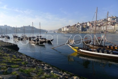 The Douro River in Porto, Portugal, underachiever's blue sky and some white clouds. Some boats can be seen carrying whine barrels