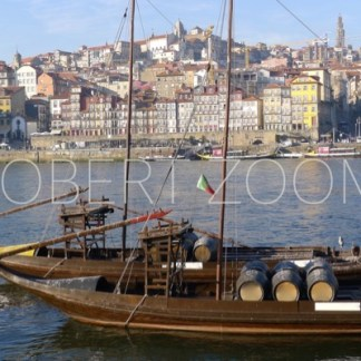 A boat carrying barrels with wine is anchored near one margin of the Douro river in the city of Porto. In the background is the old town.