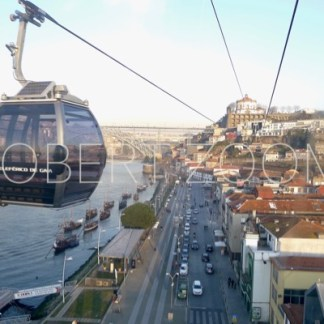 A cable car riding along the Douro river in the city of Porto, on the right side of the picture one can see an avenue and many constructions