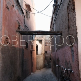 Inside the Medina in Marrakech, Morocco, this narrow passage is deserted and a bicycle leans against the right wall