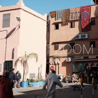 Rugs are hanging from the facade top of a building in Marrakech, Morocco, while some people walk on the street in front of it