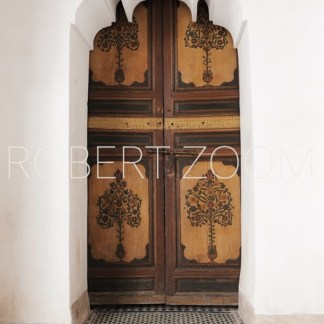 Arabic wooden door decorated with drawings, inside a white wall