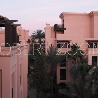 Pink color modern arabic buildings in Marrakech, Morocco, with some trees and vegetation between them