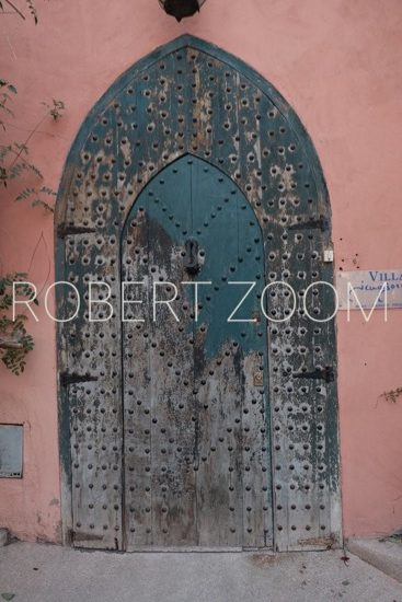 An old wooden arabic door, set on a pink colored wall, in Marrakech, Morocco.