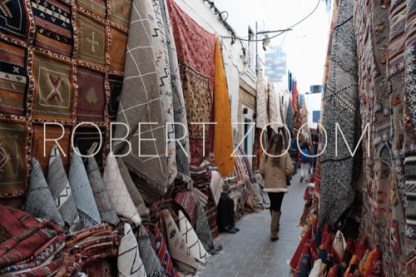 Oriental rugs ,hanging on walls along a narrow alley in Marrakech. A vendor is sitting in front of the rugs, looking at the passersby.