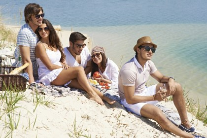 Young people having picnic near the coastline