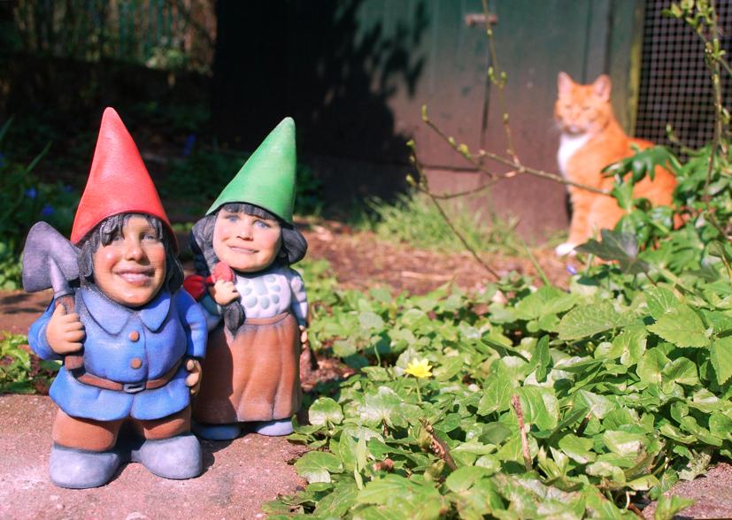 Twee 3D-geprinte gepersonaliseerde tuinkabouters in een tuin met in de achtergrond een rode kat.