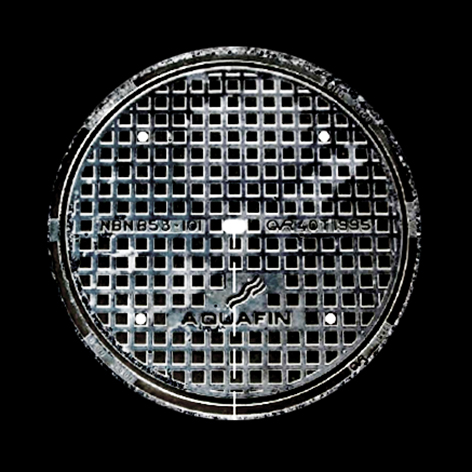 Een zwart-wit foto van een putdeksel van het Aquafin rioolstelsel. Achtergrond is zwart.
