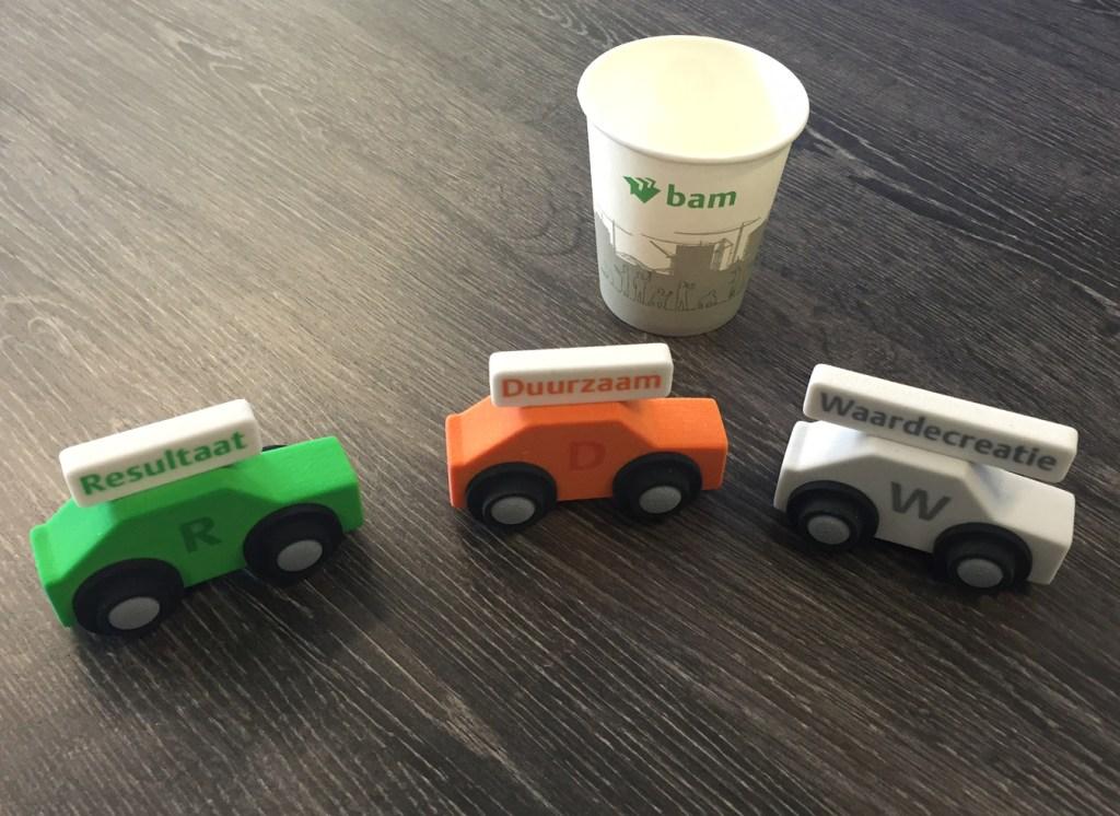 3D-geprinte presentatie-modellen in de vorm van speelgoedautootjes plus een koffiebekertje op een houten tafelblad.