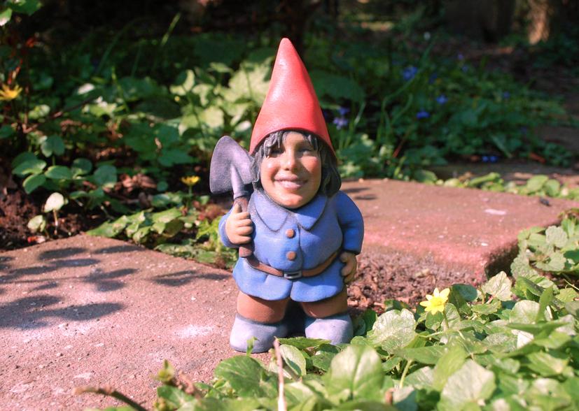 Een 3D-geprinte gepersonaliseerde tuinkabouter (jongen) in een tuin op een tegel, tussen het gras.