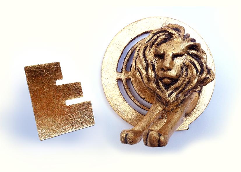 Een in plastic 3D-geprinte en 'vergulde' Effie Award en Lion Award op een witte achtergrond.