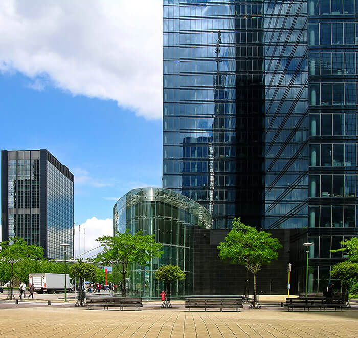 Tall city buildings with paved area and trees