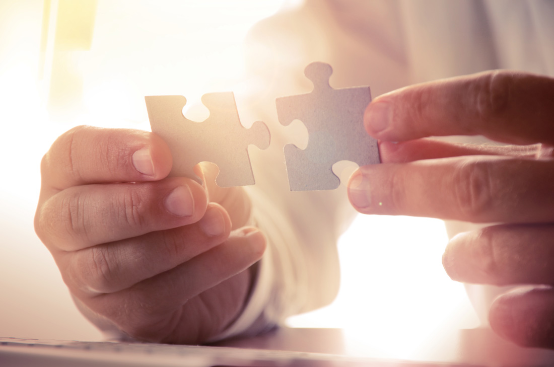 Man putting two jigsaw pieces together
