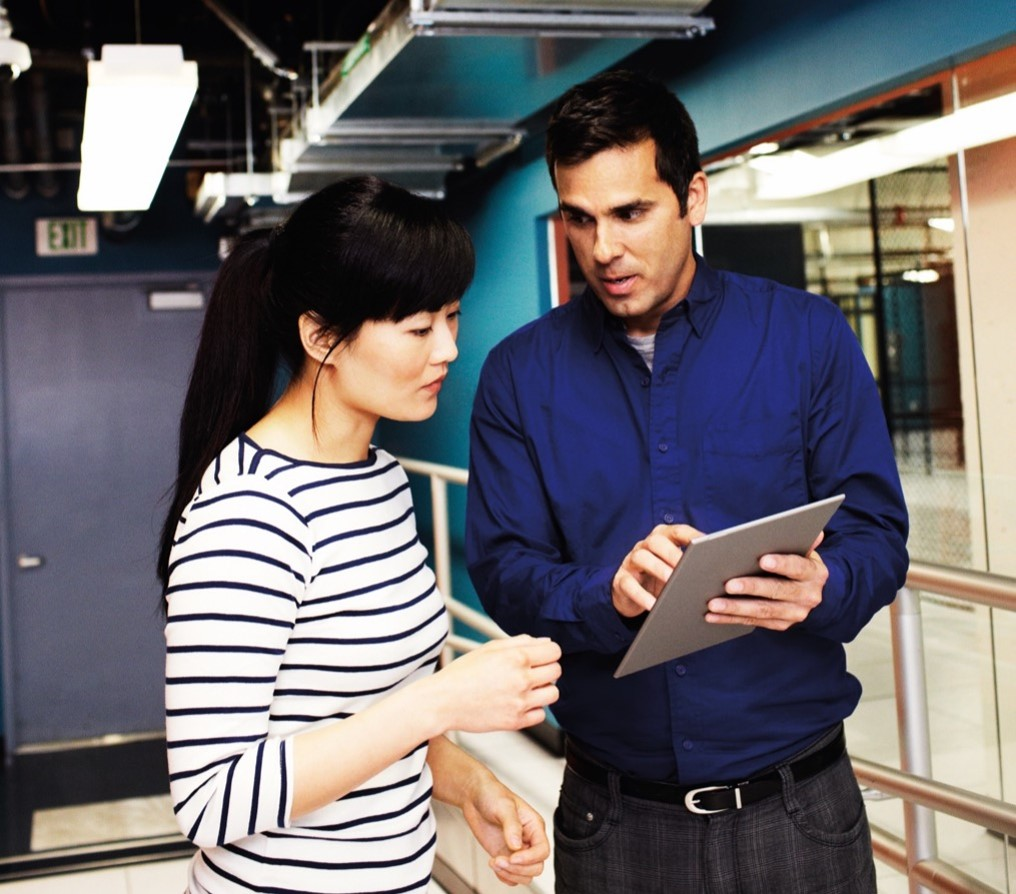 Man pointing to a mobile device screen with a woman looking
