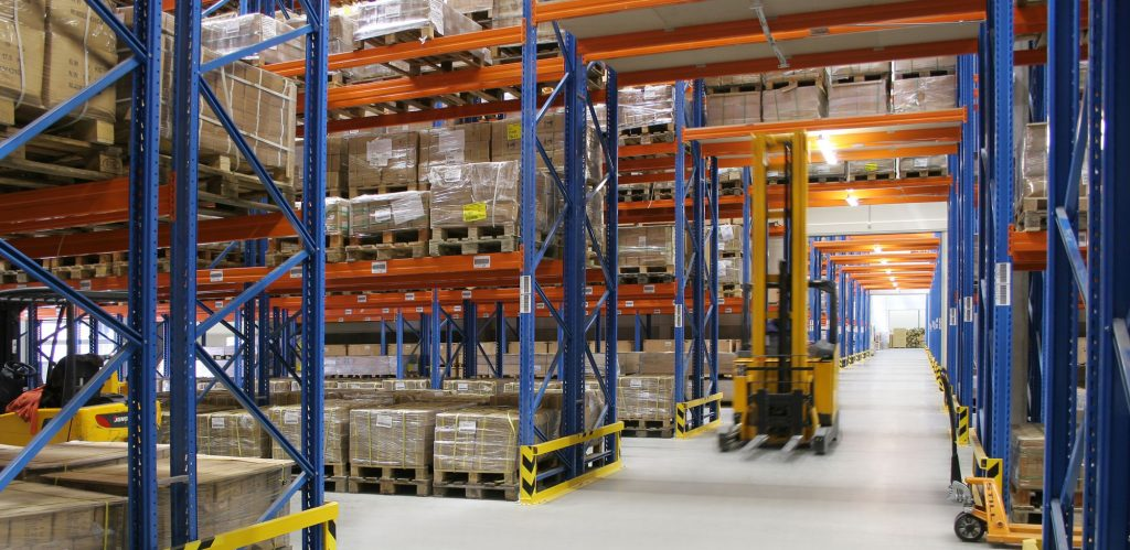 Blue metal storage shelves in warehouse with forklift