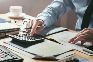 Business man tapping on calculator with spreadsheets on desk