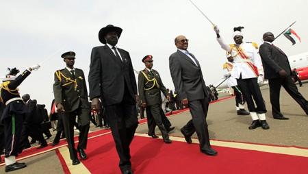 South Sudan's President Salva Kiir inspects the guard of honour with Sudan's President Omar al-Bashir as he arrives for talks at Khartoum Airport