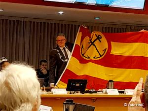 Burgemeester Schuiling met de vlag van Den Helder (foto HMC)