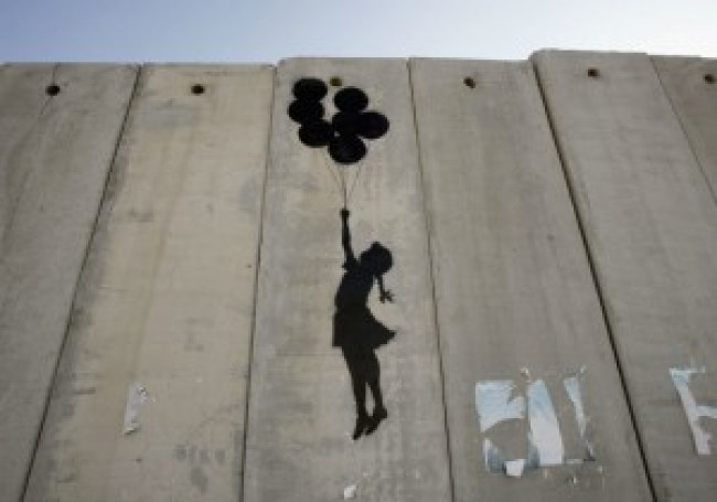 A graffiti titled Balloon Debate by Banksy, seen on August 6, 2005 on Israel's security barrier in Ramallah, West Bank (foto Marco di Lauro, Getty Images)