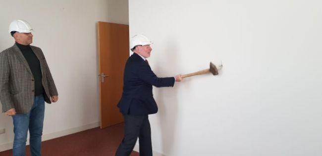 Direceur Ult van de Wal van bouwbedrijf L. van der Wal & Zn. BV kijkt toe hoe wethouder Michiel Wouters een gipsen tussenwand aanpakt met een moker (foto NHD)